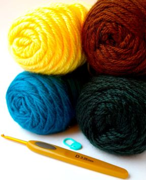 Yarn, crochet hook, and marker used in crocheting Bitzer, character from Shaun the Sheep